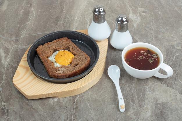 Jajka tostowe i filiżankę herbaty na marmurze z przyprawami. wysokiej jakości zdjęcie