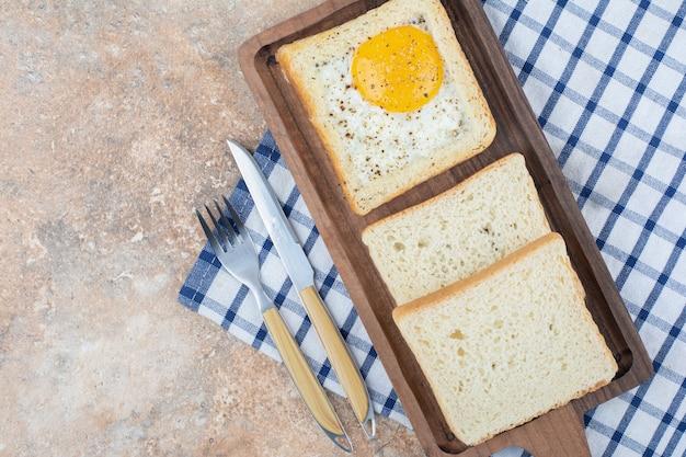 Jajka tosty z przyprawami na drewnianej desce ze sztućcami