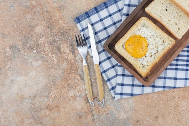 Jajka tosty z przyprawami na drewnianym talerzu ze sztućcami