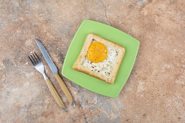 Jajka tosty z przyprawami na zielonym talerzu ze sztućcami