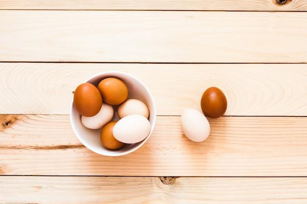 Jajka w ceramicznej misce, talerz na drewnianym tle, przygotowanie do wielkanocy, produkty rolne, kurczak i jajko, dekorowanie domu na wakacje