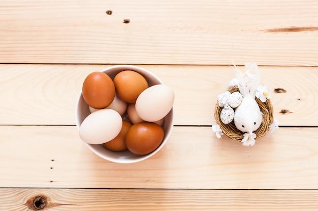 Jajka w ceramicznej misce, talerz na drewnianym tle, przygotowanie do wielkanocy, produkty rolne, kurczak i jajko, figurka ptaka w gnieździe, dekoracja domu
