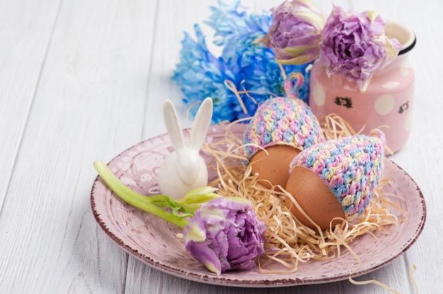 Jajka w dzianych czapkach, kwiatach i ozdobnym króliku