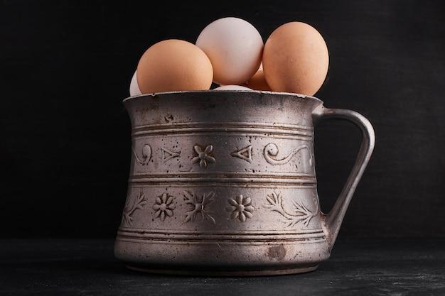 Jajka w etnicznym metalowym słoju.