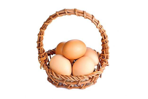 Jajka w koszu na białym tle