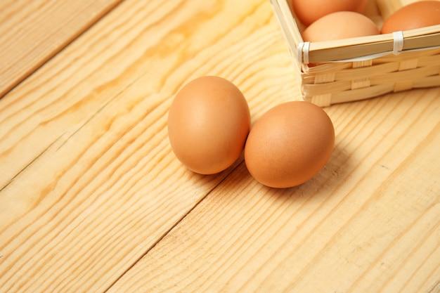 Jajka w koszu na drewnianym stołowym tle.