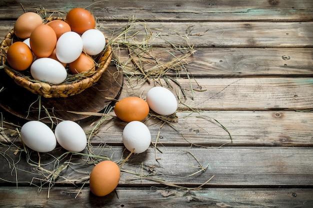 Jajka w koszu. na drewnianym tle.