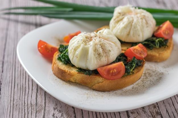 Jajka w koszulce z chlebem i pomidorami na talerzu na drewnianym stole. wegetariańska przekąska z jajkiem w koszulce.