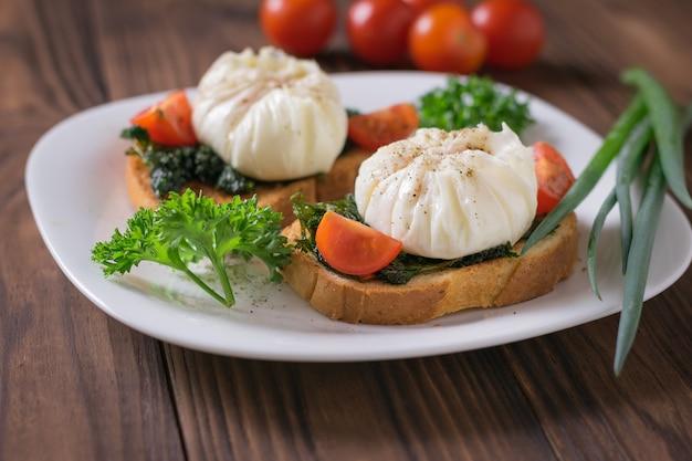 Jajka w koszulce z kromkami chleba i pęczkiem zielonej cebuli na białym talerzu. wegetariańska przekąska z jajkiem w koszulce.