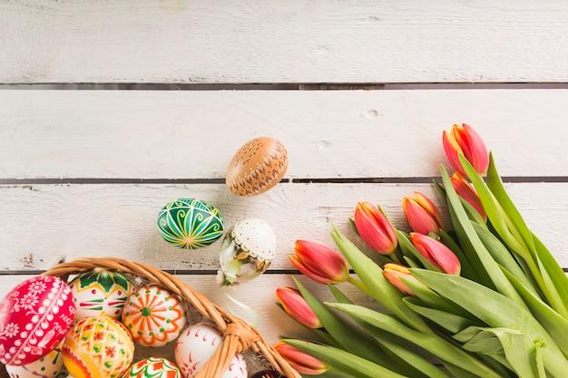 Jajka w koszyku w pobliżu tulipanów
