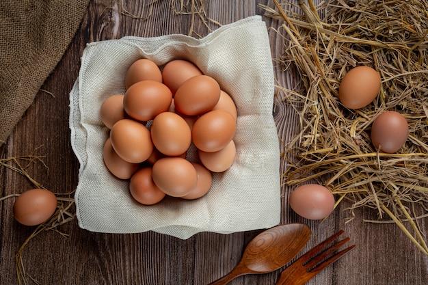 Jajka w kubkach na płótnie z suchą trawą.