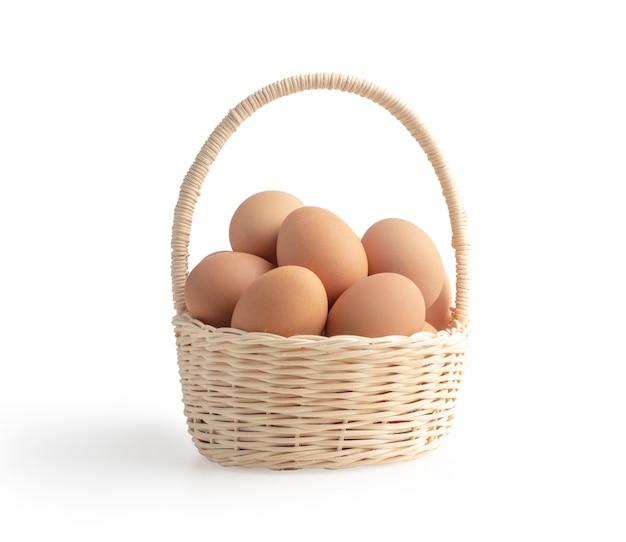 Jajka w łozinowym koszu odizolowywającym na białym tle