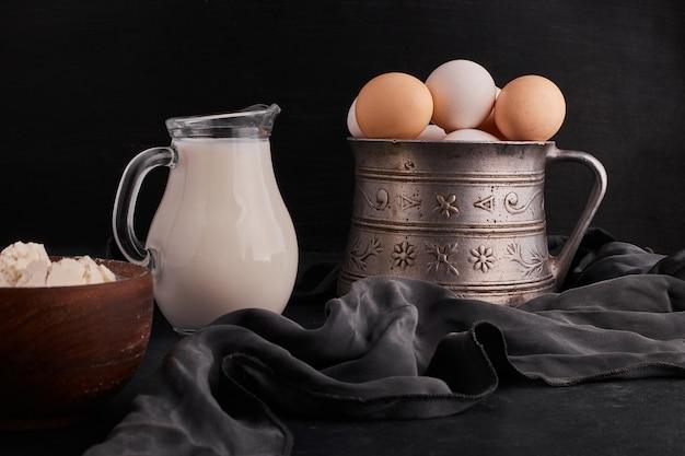 Jajka w metalowym garnku ze słoikiem mleka na bok.