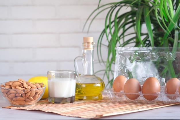 Jajka w plastikowym pojemniku mleko i orzech migdałowy na stole