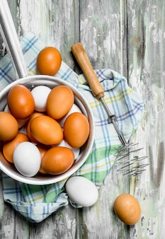 Jajka w rondlu z trzepaczką na serwetce. na rustykalnym tle.