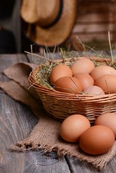 Jajka w wiklinowym koszu na stole zbliżenie