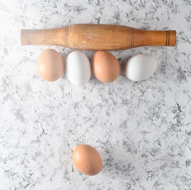 Jajka, wałek do ciasta na białej powierzchni betonowej