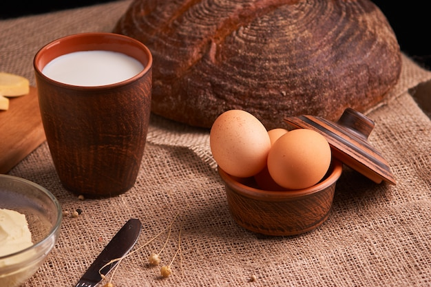 Jajka z chlebem i kuchennymi naczyniami na rocznika drewnianym tle. smaczne jedzenie