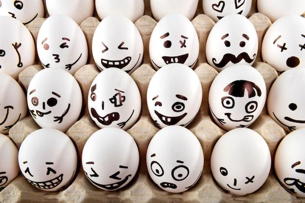 Jajka z kreskówek twarze w zasobniku.