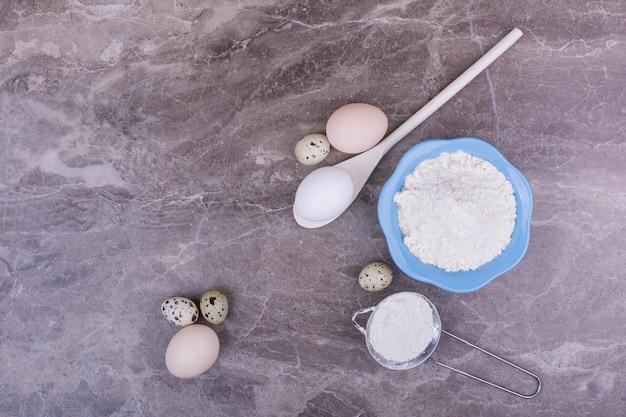 Jajka z kubkiem mąki na ziemi.