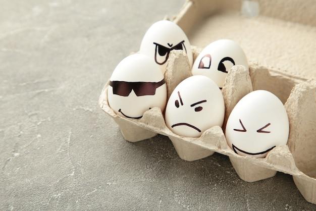 Jajka z różnymi emocjami na twarzy. kompozycja wielkanocna z miejsca na kopię na szarym tle