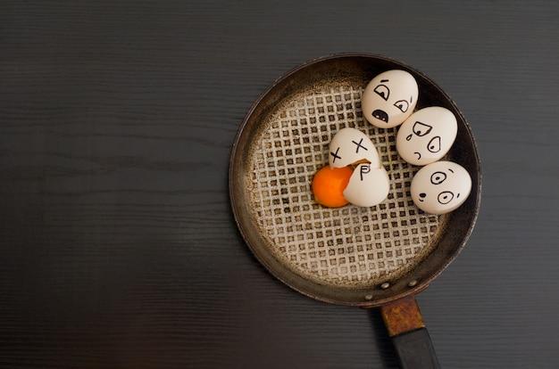 Jajka z rysowanymi emocjami, połamane jajko na środku patelni, czarny stół