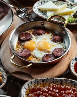 Jajka z widokiem z góry z kiełbasami i serem na brązowym drewnianym biurku śniadanie posiłek jedzenie
