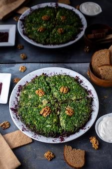 Jajka z zieleniną kuku witamina bogata w smaczne z zaprojektowanymi orzechami na szarym biurku