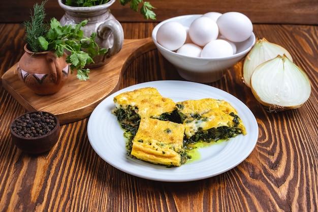 Jajka ze szpinakiem, cebula, zieleń, przyprawy, widok z boku