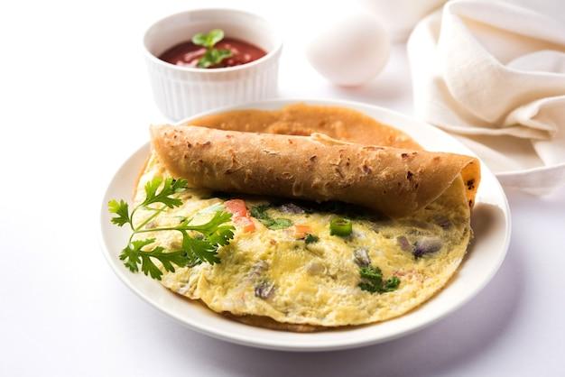 Jajko chapati - omlet rolka lub franky. indian popularny, szybki i zdrowy przepis na tiffin lub lunch box dla dzieci. podawane na nastrojowym tle. selektywne skupienie