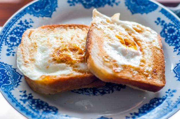 Jajko chleb na talerzu, fotografowane z naturalnego światła. złote francuskie tosty z masłem i jajkiem. śniadanie z chlebem. angielskie śniadanie. zdrowe śniadanie z jajkami