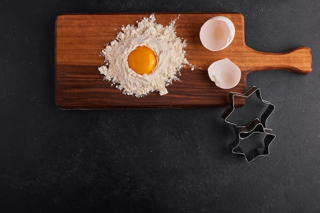 Jajko i mąka zmieszane ze sobą na desce, widok z góry.