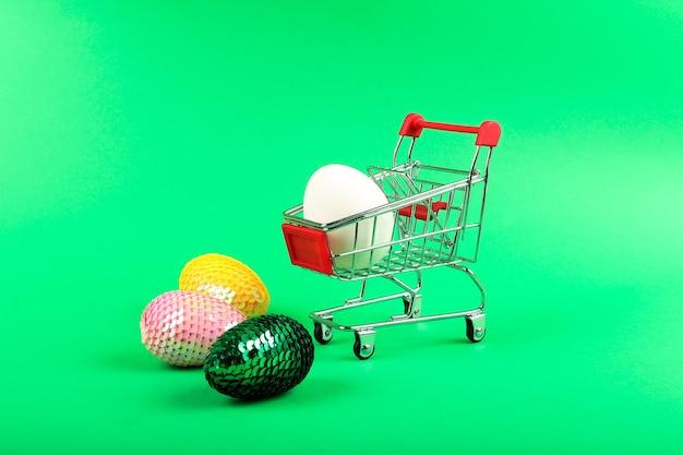 Jajko kurze leżące w wózku na zakupy i błyszczące sztuczne jajka wielkanocne w pobliżu
