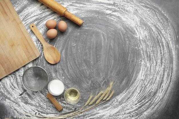 Jajko kurze, mąka, oliwa z oliwek, mleko, kłosy pszenicy, narzędzie kuchenne na szarym tle stołu.