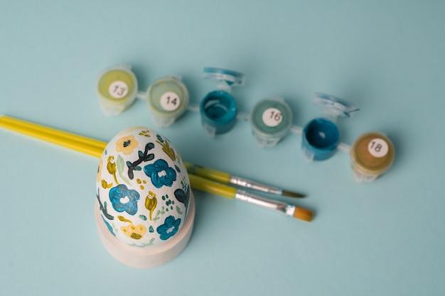 Jajko kurze malowane w kwiatowy wzór. dekoracja botaniczna. minimalne jajko wielkanocne na niebieskim tle.