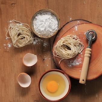 Jajko, mąka i surowy azjatycki makaron na drewnianej desce