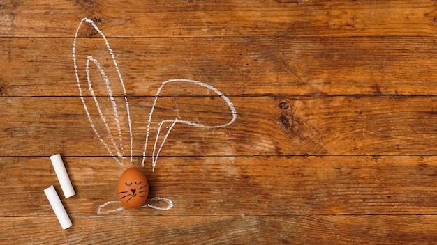 Jajko na drewnianej powierzchni. rysowane kredą uszy i pomalowany pysk. widok z góry i miejsce na tekst. kartka wielkanocna i baner