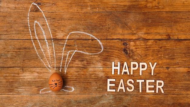 Jajko na drewnianej powierzchni. rysowane kredą uszy i pomalowany pysk
