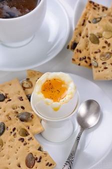 Jajko na miękko z filiżanką kawy i krakersami na śniadanie