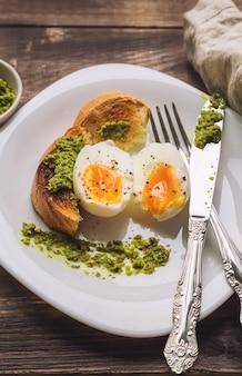 Jajko na miękko z opiekanym chlebem i sosem pesto na rustykalnym drewnianym tle