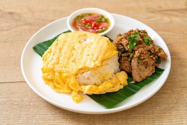 Jajko na posypanym ryżem z grillowaną wieprzowiną i ostrym sosem. azjatycki styl żywności
