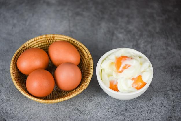 Jajko na twardo w misce i świeże jajka w koszyku