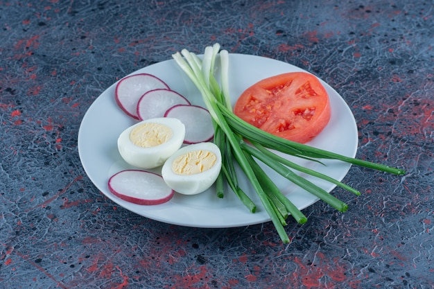 Jajko na twardo z pokrojonym pomidorem i rzodkiewką.