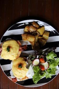 Jajko po benedyktyńsku z bekonem i ziemniakami na tle drewna