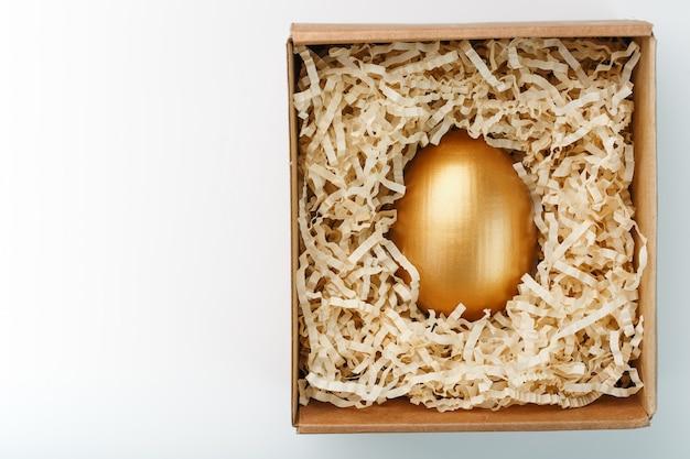 Jajko robić złoto w drewnianym pudełku na białym tle. pojęcie wyłączności i superprize. minimalistyczna kompozycja.