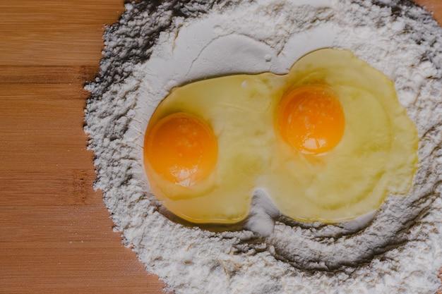 Jajko rozbite na mące, środek do wypieku chleba. close-up surowego żółtka na mąkę z selektywnym fokusem