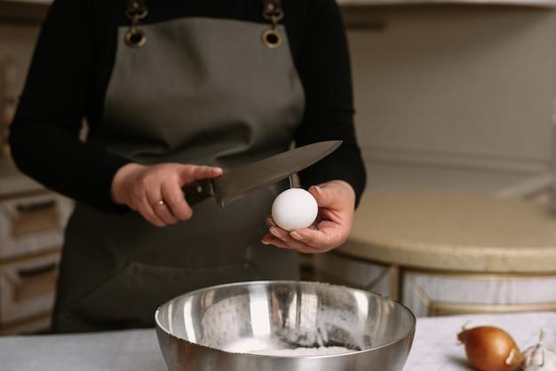 Jajko rozbite z żółtkiem w misce z mąką. przepis na ciasto.