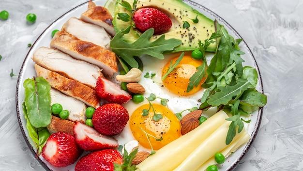 Jajko sadzone, awokado, truskawka, grillowany filet z kurczaka, ser, orzechy i rukola. dieta keto. zdrowe śniadanie lub obiad. widok z góry.