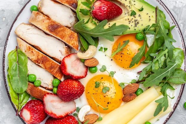 Jajko sadzone, awokado, truskawka, grillowany filet z kurczaka, ser, orzechy i rukola. dieta ketogeniczna. koncepcja zdrowej żywności, widok z góry