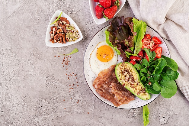 Jajko sadzone, bekon, awokado, rukola i truskawki